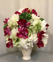 cymbidium orchid hydrangea and sedum plant arrangement in cream