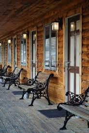 a porch swing on a wooden porch of a log cabin stock photo