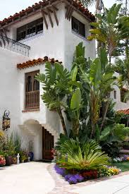 old california and spanish revival style home with tropical