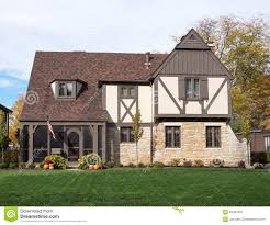 english tudor home with american flag u0026 pumpkins stock photo