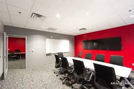 small conference room in an office space with red accent wall and