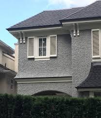 grey stucco white windows and trim black roof u0026 gutters heavy