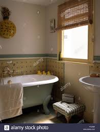 small traditional bathrooms small upholstered stool beside roll top bath in a traditional stock