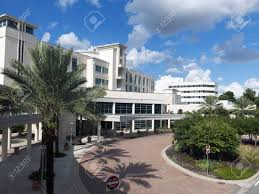 front entrance to a modern hospital with palm tree landscaping