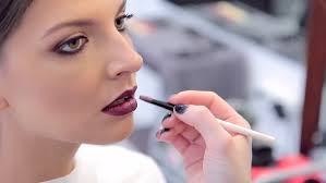 looking for makeup artist woman plays with makeup brush looking at creative