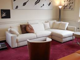 impressive maroon rug lies on floor under white l shaped sofa with
