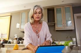 une femme plus âgée après recette dans la cuisine sur le comprimé