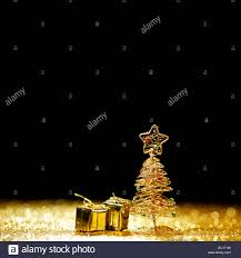 decorative golden toy christmas tree and gifts on black background