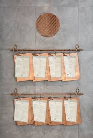 these menus on copper clipboards are hung on a copper pipe