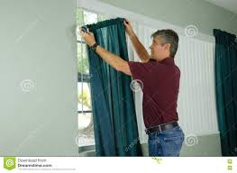 man hanging curtains home repair maintenance stock photo image