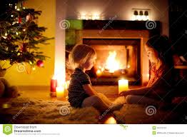 happy sisters by a fireplace on christmas stock photo image