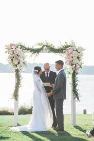 blush and ivory flower decorated wooden wedding arch