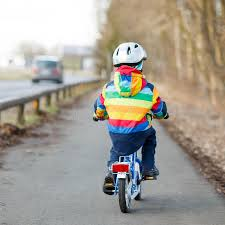 raincoat for bike riders kid boy in safety helmet and colorful raincoat riding bike outd