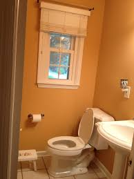 orange painted bathroom wall with white stained wooden glass