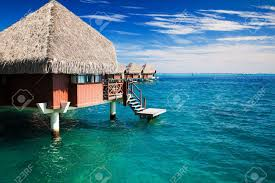 over water bungalow with steps into green clear ocean stock photo