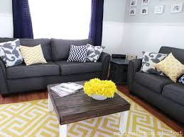 yellow and grey living room white walls bright yellow plant on