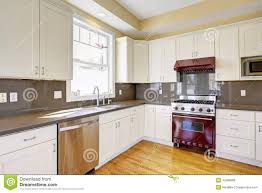 white kitchen with burgundy stove and grey counter tops stock