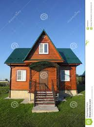 wooden house with green metal roof front on view stock photo
