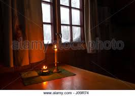 a candle in the window of a cabin snow covered