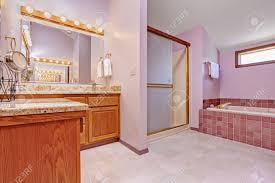 bathroom interior in light pink tone with tile trim shower