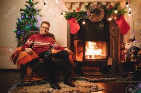 happy man in red sweater sitting in front of the fireplace