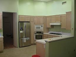 smooth green wall theme and brown wooden kitchen cabinet connected