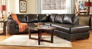 black distressed leather sectional on brown laminated wooden floor