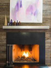 silver steel mantel shelf with black fireplace on grey stone wall