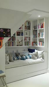 utilize spaces under stairs with wall built in bookshelf and bench