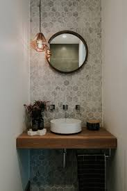 stunning powder room with marble hexagon wall tiles round mirror