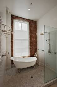 bathroom airy bathroom with brick wall near oval white clawfoot