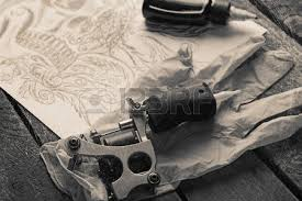 tattoo machine sketch and tattoo supplies on old wooden table