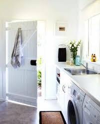 crisp white laundry room by kelly nutt design design beach