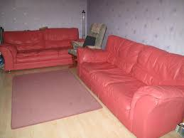 two 3 seaters dfs coral pink leather sofa in shirley west