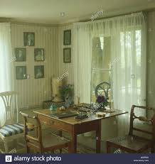 antique furniture in dining room with wallpaper and white voile