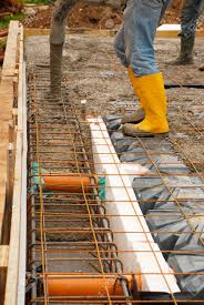 builders pour concrete onto the foundations of a small house