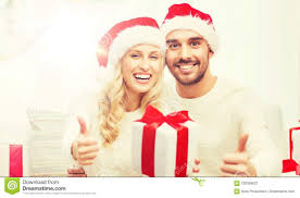 happy couple with christmas gifts and thumbs up stock photo