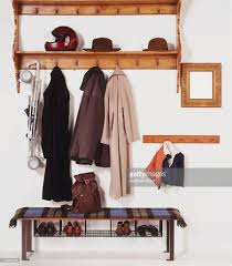 wooden coat and hat rack with shelves hats and helmet on shelf