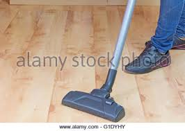 vacuuming of laminate floor by vacuum cleaner at home stock photo