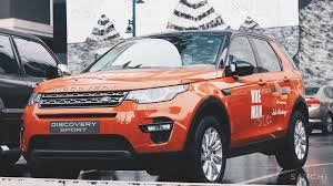 orange land rover discovery play for the human race