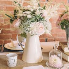 enamel jugs of pink and cream flowers were used as tablecentres in