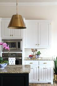 white kitchen black island brass pendant lights in the kitchen dimples and tangles