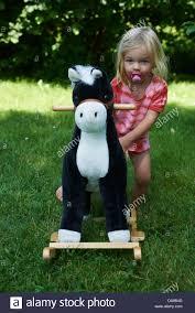 Child Blond On A Rocking Horse Outside Summer Garden Stock