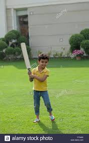 india young boy 4 5 holding cricket bat on backyard stock photo
