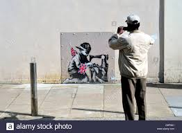 mural by the street artist banksy in islington london protected a local man photographs banksy mural in turnpike lane london uk stock photo