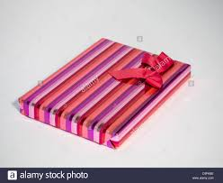 shiny wrapping paper gift wrapped in striped shiny wrapping paper with bow sat on