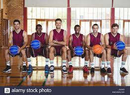 basketball player on bench portrait of smiling basketball players sitting on bench with stock