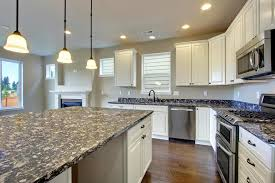 white wooden kitchen cabinet with lack cream marble counter top