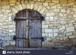old stone wall with an arched wooden door texture stock photo