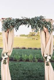 wedding arch leaves a classic fabric draped arch topped with lush eucalyptus leaves